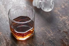 Imbottigli il whiskey ed il vetro di whiskey su fondo nero Immagine Stock