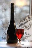 Imbottigli la bottiglia di vino rosso su priorità bassa invernale fotografia stock