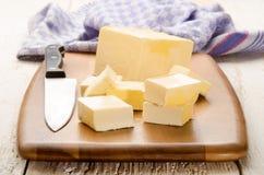 Imburri i cubi ed il coltello da cucina su un bordo di legno Immagine Stock