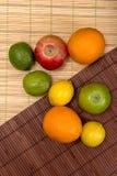 Ime,柠檬,苹果,在席子的橙色谎言 免版税库存照片