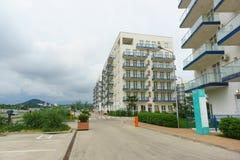 Imeretinskiy hotell, maritim fjärdedel på gataperspektivet i semesterorten av Adler Molnig sommardag Arkivfoton