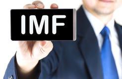 IMF,国际货币基金组织,在手机屏幕上的词 免版税图库摄影