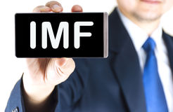 IMF, International Monetary Fund, word on mobile phone screen. In blurred young businessman hand over white background, business concept royalty free stock photography