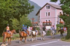Children and adults on horseback rides in heading for forest roads in the Pyrenees mountains stock photography