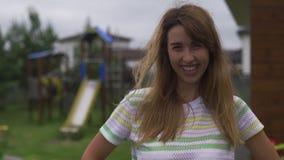 Imitador de la emoción del retrato de la mujer joven tirado en el jardín que sonríe y feliz - escena caliente del verano del colo almacen de video