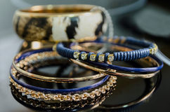 Imitation jewelry. Some shiny bracelets made in golden and blue metals. Imitation jewelry. Fake gold Royalty Free Stock Images