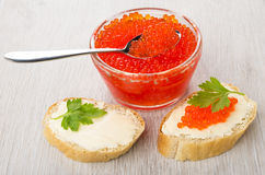 Imitation red caviar and spoon in bowl, sandwiches with butter. Imitation red caviar and spoon in transparent bowl, sandwiches with butter, parsley, spoon on Royalty Free Stock Photo