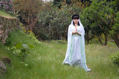 A imitation showing chinese girl. A chinese girl who dressed in ancient costume of China was imitation showing the goddess of mercy in garden Royalty Free Stock Photography