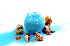 Imitation spray blue liquid in a glass globular vase. On the marine theme royalty free stock photography