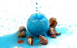 Imitation spray blue liquid in a glass globular vase. On the marine theme royalty free stock photo