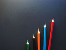 Imitation success. Business. Colored pencils on a black background Royalty Free Stock Images