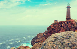 Imitation of vintage photo with the lighthouse on the rocky coas Stock Photography