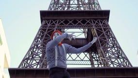 Imite en la camisa pelada que juega en el violín invisible cerca de torre Eiffel metrajes
