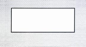 Imite encima de bandera en blanco con el marco negro en la pared de ladrillo blanca Imagenes de archivo