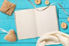 Imite encima de la libreta abierta del espacio en blanco, regalos de la Navidad en un fondo de madera de la turquesa con el espac Foto de archivo libre de regalías