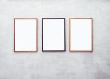 Imite encima de los carteles en blanco con el marco de madera en la pared del cemento fotos de archivo