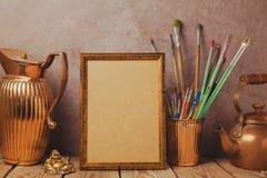 Imite encima de marco del cartel con los objetos artísticos del vintage en la tabla de madera fotos de archivo libres de regalías