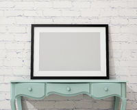 Imite encima de marco negro en blanco en el escritorio y la pared blancos, fondo Foto de archivo