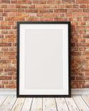 Imite encima de marco negro en blanco en la pared de ladrillo vieja y el piso de madera, fondo Imagen de archivo
