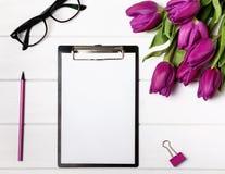 Imite para arriba con el papel en blanco, los tulipanes y los accesorios rosados Imagen de archivo libre de regalías