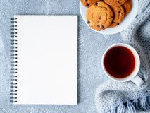 Imite para arriba con la hoja en blanco de la libreta, el té, las galletas y caliente hecha punto fotos de archivo