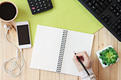 Imite para arriba de espacio de trabajo del escritorio de la tabla de la oficina con las manos que escriben en el cuaderno en bla Fotografía de archivo