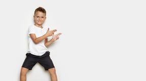 Imite para arriba de muchacho sonriente en el fondo blanco Fotografía de archivo