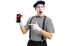 Imitieren Sie den Künstler, der das Telefon zeigt, das mit rotem Band und dem Zeigen eingewickelt wird Lizenzfreie Stockbilder