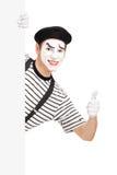 Imitieren Sie den Tänzer, der einen Daumen oben hinter einer weißen Platte gibt Stockbilder