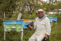 Imker in der Schutzkleidung, die Raucher bei der Stellung am Bienenhaus hält Lizenzfreies Stockfoto