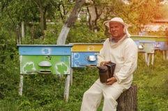 Imker in der Schutzkleidung, die Raucher bei der Stellung am Bienenhaus hält Lizenzfreie Stockfotos