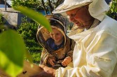 Imkergroßvater und -enkel überprüfen einen Bienenstock von Bienen Lizenzfreie Stockbilder