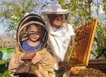 Imkergroßvater und -enkel überprüfen einen Bienenstock von Bienen Stockbilder