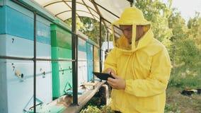 Imkermens die met tabletcomputer houten bijenkorven controleren alvorens honing in bijenstal te oogsten stock videobeelden