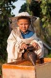 Imkerportret van een jonge jongen die ter beschikking in de bijenstal bij bijenkorf met roker voor bijen werkt Royalty-vrije Stock Foto