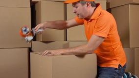 Immagazzini il lavoratore in cartone grande d'imballaggio uniforme dell'arancia con la pistola del nastro di condotta Il multiplo video d archivio