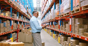 Immagazzini il lavoratore che per mezzo della compressa digitale mentre controllano i pacchetti stock footage