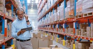 Immagazzini il lavoratore che per mezzo della compressa digitale mentre controllano i pacchetti video d archivio