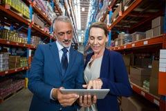 Immagazzini il responsabile ed il cliente che discutono sopra la compressa digitale immagini stock libere da diritti