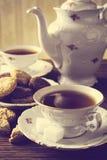 Immagine antiquata con due tazze di effetto d'annata del tè con i biscotti immagine stock