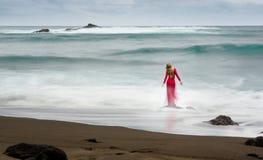 Immagine artistica di arti circa bella una donna bionda vestita rossa e lunga, che sta su una roccia della spiaggia nell'acqua fotografie stock