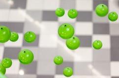 Immagine astratta delle sfere di verde 3d che cadono sul fondo grigio Fotografie Stock
