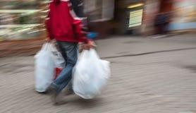 Immagine astratta di un uomo in abiti sportivi con i sacchetti di plastica di compera Fotografia Stock Libera da Diritti