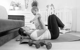 Immagine in bianco e nero della giovane donna che si esercita con i suoi 9 mesi del figlio del bambino a casa Fotografia Stock Libera da Diritti