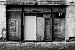 Immagine in bianco e nero di una finestra dilapidata con i ciechi fatti delle tavole di legno Immagine Stock Libera da Diritti
