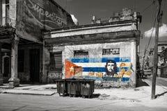 Immagine in bianco e nero di vecchie costruzioni misere a Avana con una pittura di Che Guevara e di una bandiera cubana Immagine Stock
