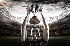 Immagine composita 3D del ritratto di riuscito trofeo della tenuta del giocatore di rugby Immagini Stock