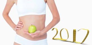 immagine composita 3D della donna che tiene una mela davanti alla sua pancia Fotografia Stock Libera da Diritti