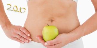 immagine composita 3D della donna di misura che tiene una mela davanti alla sua pancia Fotografia Stock