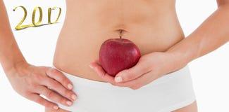 immagine composita 3D della donna di misura che tiene una mela davanti alla sua pancia Fotografia Stock Libera da Diritti